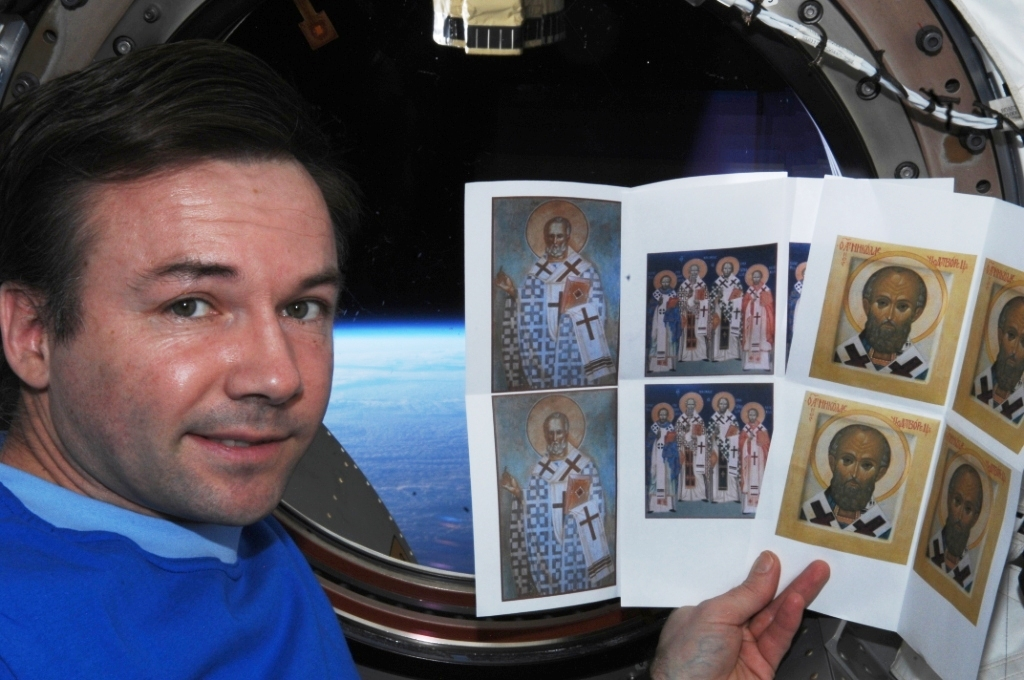 A cosmonaut on ISS with printed icons